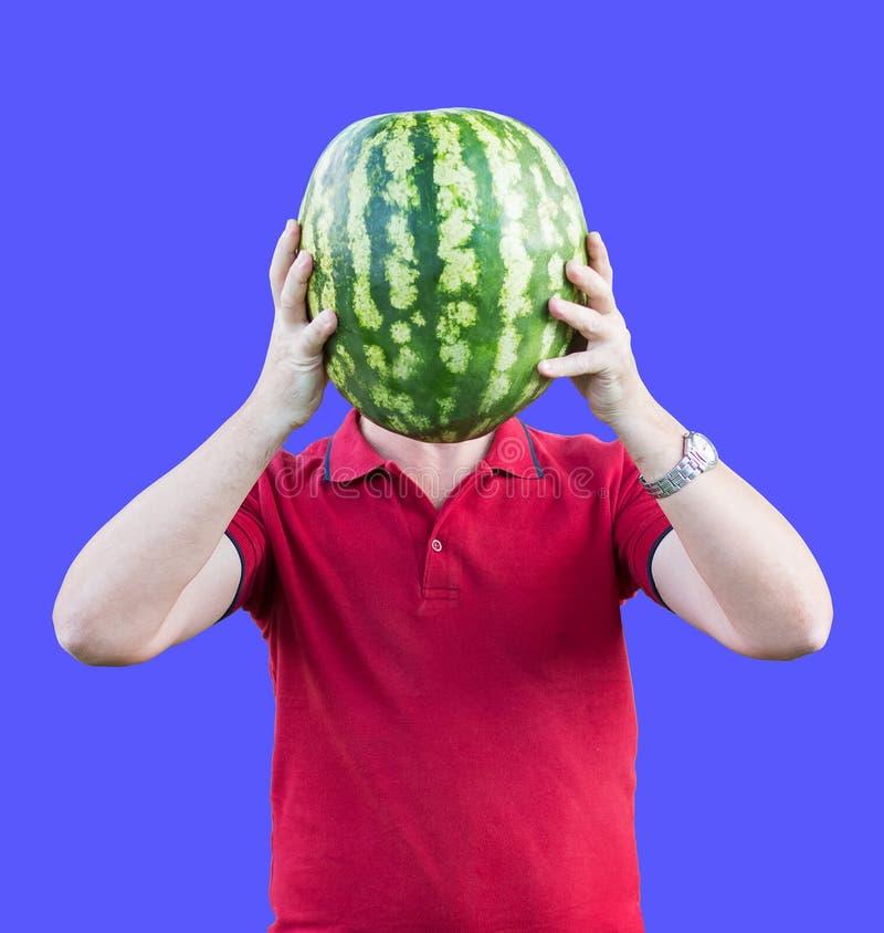 Ένα άτομο κρατά στο επίπεδο του κεφαλιού ενός ώριμου νόστιμου καρπουζιού Καρπούζι αντί του κεφαλιού Διαφήμιση των καρπουζιών στοκ φωτογραφία με δικαίωμα ελεύθερης χρήσης