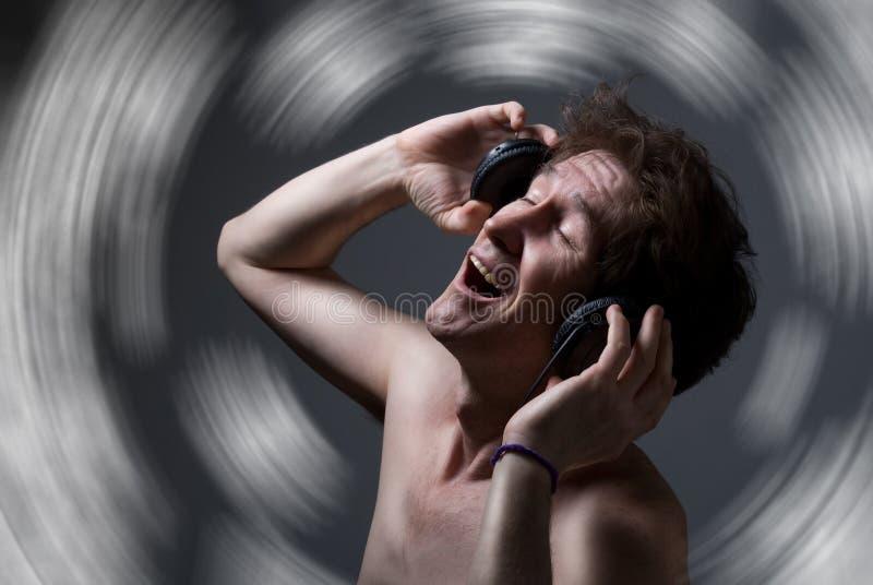 Ένα άτομο με έναν γυμνό κορμό που ακούει τη μουσική με τα ακουστικά στοκ εικόνα με δικαίωμα ελεύθερης χρήσης