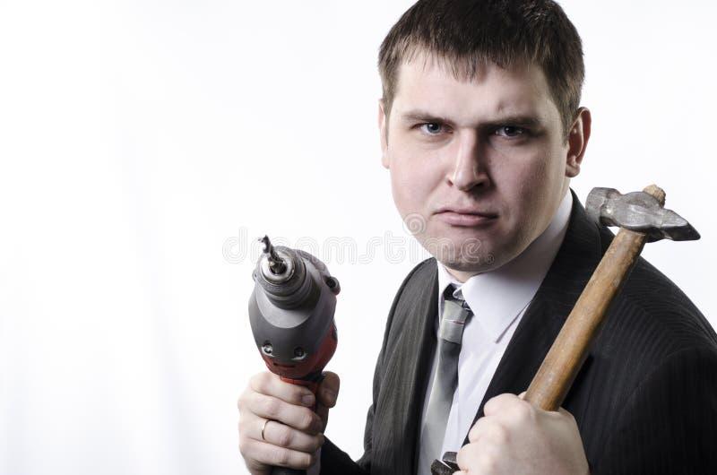 Ένα άτομο με ένα σφυρί και ένα τρυπάνι στοκ εικόνα