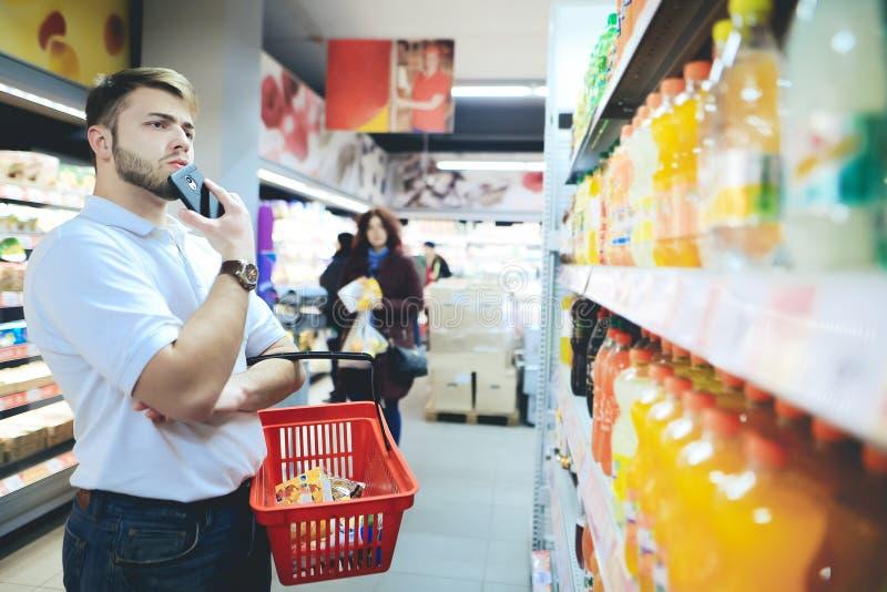 Ένα άτομο με ένα καλάθι στα χέρια του εξετάζει τα ποτά στην υπεραγορά Ένα άτομο με μια γενειάδα αγοράζει τα τρόφιμα σε μια υπεραγ στοκ φωτογραφία με δικαίωμα ελεύθερης χρήσης