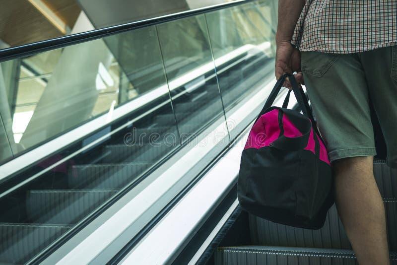 Ένα άτομο με μια τσάντα σε ένα ταξίδι γίνεται κατανοητό στην κυλιόμενη σκάλα στοκ φωτογραφία με δικαίωμα ελεύθερης χρήσης