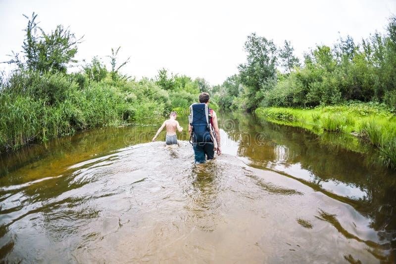 Ένα άτομο με παιδιά διασχίζει τη διάβαση ποταμών στοκ εικόνες