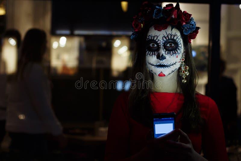 Ένα άτομο με ένα χρωματισμένο πρόσωπο ενός σκελετού, ένα νεκρό zombie, στην πόλη κατά τη διάρκεια της ημέρας ημέρα όλων των ψυχών στοκ φωτογραφία