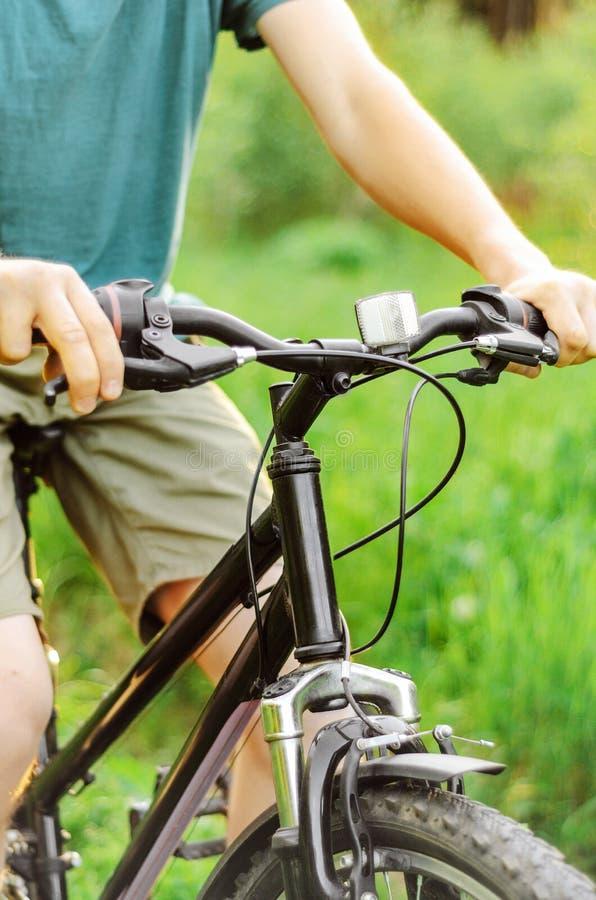 Ένα άτομο οδηγά ένα ποδήλατο βουνών σε ένα καλοκαίρι που ο δασικός δρόμος, κρατά το φρένο στοκ φωτογραφία με δικαίωμα ελεύθερης χρήσης