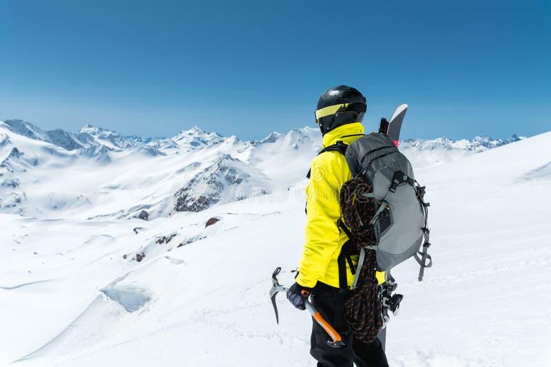 Ένα άτομο ορεσιβίων κρατά ένα τσεκούρι πάγου υψηλό στα βουνά που καλύπτονται με το χιόνι πίσω όψη υπαίθριος ακραίος υπαίθριος στοκ εικόνες με δικαίωμα ελεύθερης χρήσης