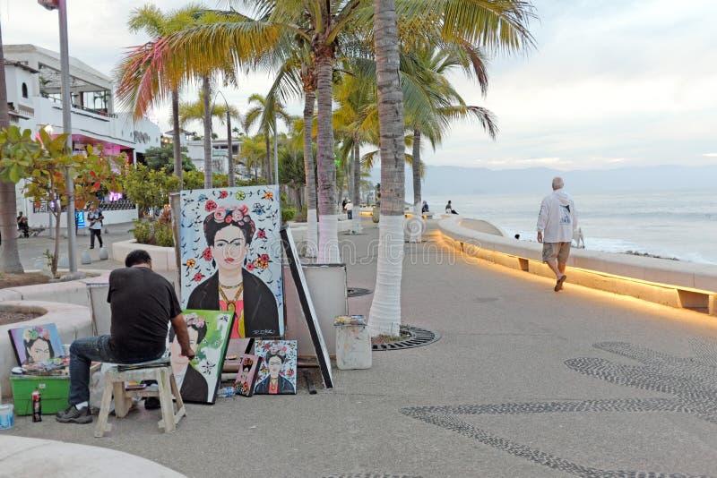 Ένα άτομο περπατά κατά μήκος του seawall δεδομένου ότι ένας καλλιτέχνης δημιουργεί τα έργα ζωγραφικής Frida Kahlo στοκ εικόνες