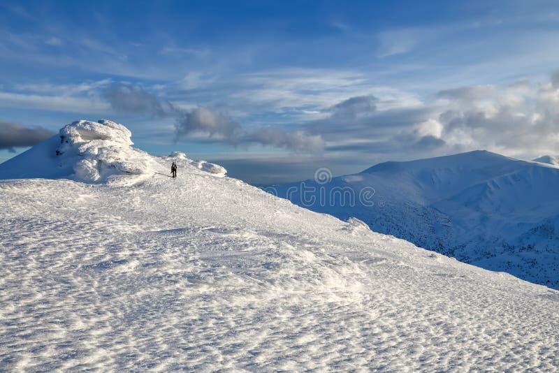 Ένα άτομο πηγαίνει κατά μήκος της πορείας με ένα σακίδιο πλάτης Μυστήριοι φανταστικοί βράχοι που παγώνουν με τον πάγο και το χιόν στοκ εικόνες με δικαίωμα ελεύθερης χρήσης