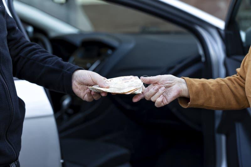 Ένα άτομο πληρώνει το αυτοκίνητο σε μια ηλικιωμένη κυρία στοκ φωτογραφίες με δικαίωμα ελεύθερης χρήσης