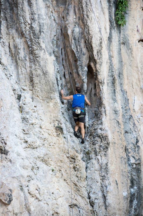 Ένα άτομο που αναρριχείται επάνω απότομους βράχους στους απότομους ασβεστόλιθων στοκ εικόνες