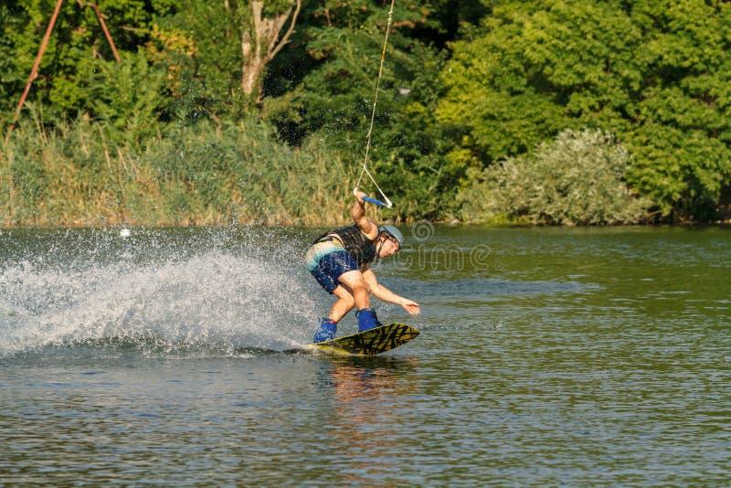 Ένα άτομο που ασχολείται με το wakeboard στη λίμνη εκτελεί τα άλματα στοκ εικόνες με δικαίωμα ελεύθερης χρήσης