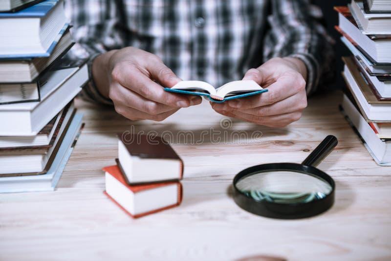 Ένα άτομο που διαβάζει ένα μικροσκοπικό βιβλίο μεταξύ των μεγάλων βιβλίων στη βιβλιοθήκη στοκ φωτογραφία με δικαίωμα ελεύθερης χρήσης