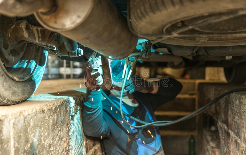 Ένα άτομο που εργάζεται κάτω από το αυτοκίνητο στοκ φωτογραφία