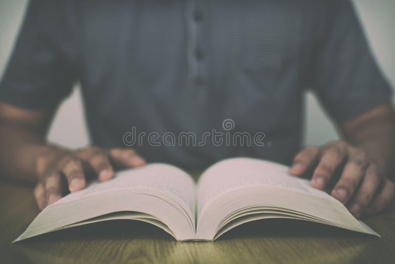 Ένα άτομο που διαβάζει ένα βιβλίο στον ξύλινο πίνακα με το εκλεκτής ποιότητας φίλτρο θόλωσε το υπόβαθρο στοκ φωτογραφίες