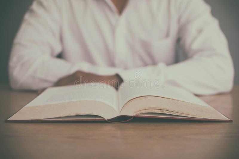 Ένα άτομο που διαβάζει ένα βιβλίο στον ξύλινο πίνακα με το εκλεκτής ποιότητας φίλτρο θόλωσε το υπόβαθρο στοκ φωτογραφία