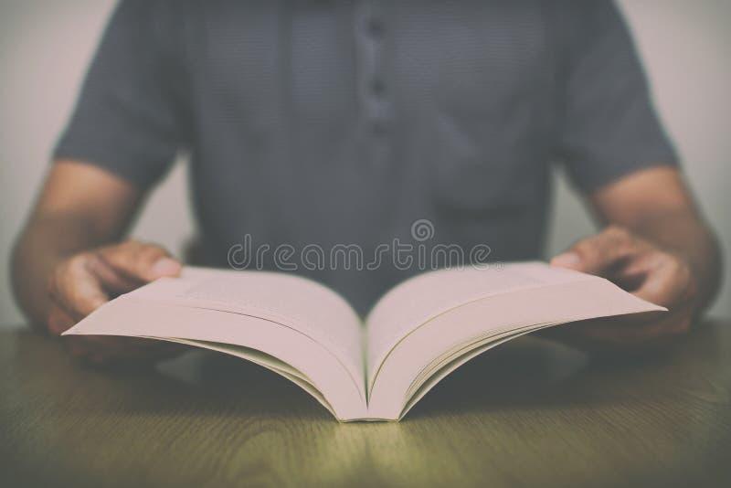 Ένα άτομο που διαβάζει ένα βιβλίο στον πίνακα με το εκλεκτής ποιότητας φίλτρο θόλωσε το υπόβαθρο στοκ φωτογραφίες με δικαίωμα ελεύθερης χρήσης