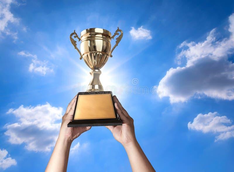 ένα άτομο που κρατά ψηλά ένα χρυσό φλυτζάνι τροπαίων με τον ουρανό και τον ήλιο bluse backgr στοκ εικόνα με δικαίωμα ελεύθερης χρήσης