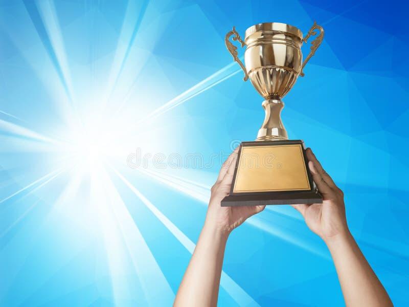 ένα άτομο που κρατά ψηλά ένα χρυσό φλυτζάνι τροπαίων με το αφηρημένο μπλε φως και στοκ φωτογραφίες με δικαίωμα ελεύθερης χρήσης