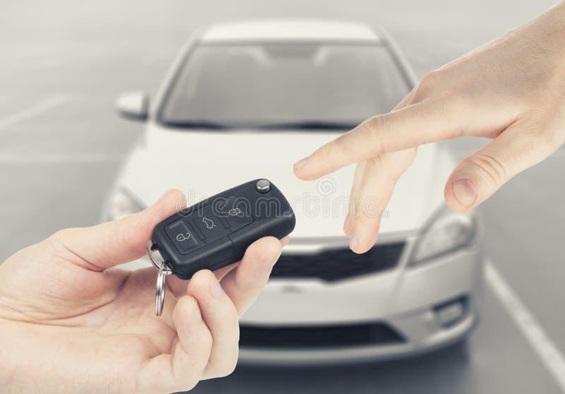 Ένα άτομο που περνά τα κλειδιά αυτοκινήτων σε ένα άλλο πρόσωπο με το αυτοκίνητο στο υπόβαθρο στοκ εικόνα με δικαίωμα ελεύθερης χρήσης
