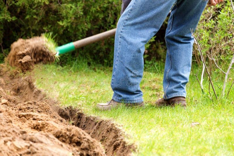 Ένα άτομο που σκάβει στο χώμα κήπων. στοκ φωτογραφία