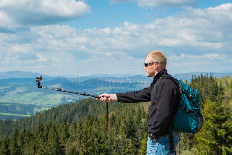 Ένα άτομο που στέκεται στην κορυφή του υψηλού λόφου με τη κάμερα δράσης - που κάνει selfie, υψηλή στα βουνά όμορφα φύση και σύννε στοκ φωτογραφία με δικαίωμα ελεύθερης χρήσης