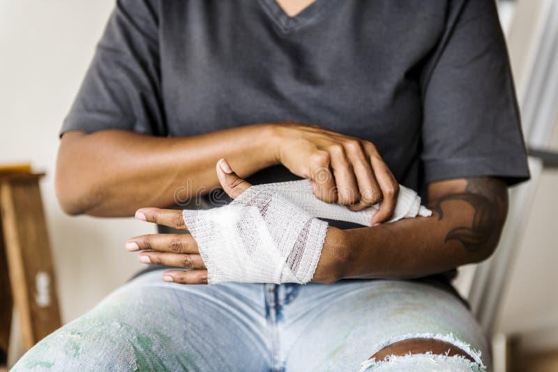 Ένα άτομο που τυλίγει το χέρι του με έναν επίδεσμο στοκ εικόνες
