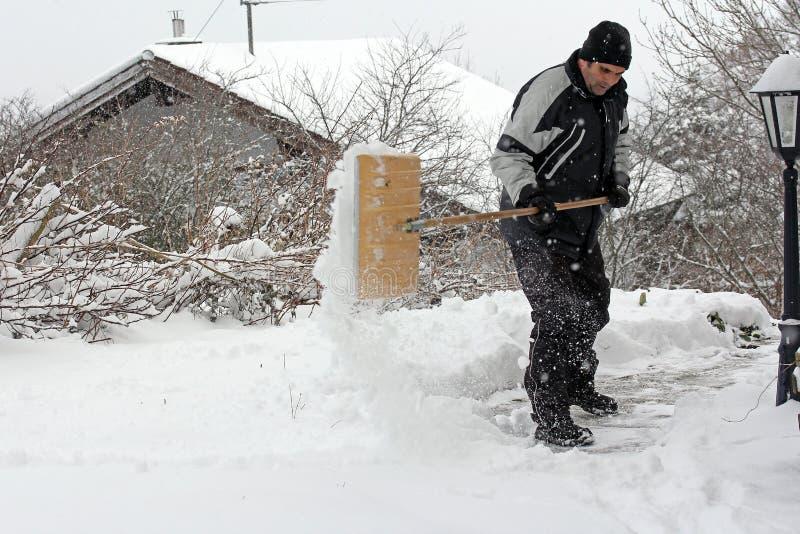 Ένα άτομο που φτυαρίζει το χιόνι στοκ φωτογραφίες