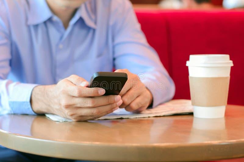Ένα άτομο που χρησιμοποιεί το έξυπνο τηλέφωνο στη καφετερία στοκ φωτογραφία