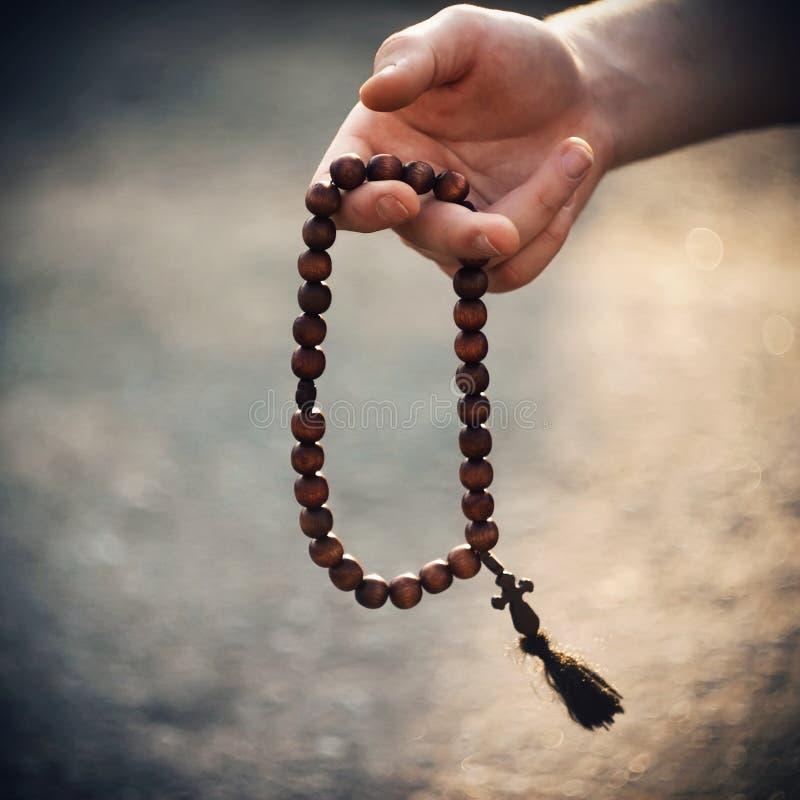 Ένα άτομο προσεύχεται το κράτημα rosary στο χέρι του στοκ φωτογραφία με δικαίωμα ελεύθερης χρήσης
