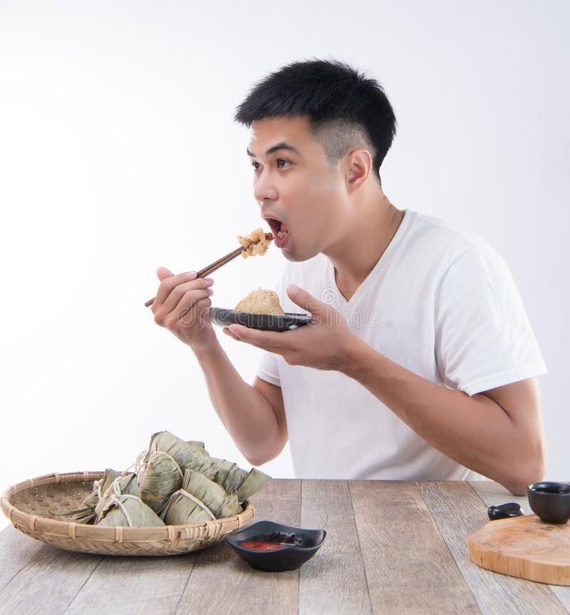 Ένα άτομο πρόκειται να φάει την εύγευστη μπουλέττα zongzirice στο φεστιβάλ βαρκών δράκων, ασιατικά παραδοσιακά τρόφιμα στοκ εικόνα