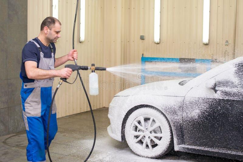 Ένα άτομο πλένει ένα μαύρο αυτοκίνητο στοκ φωτογραφία