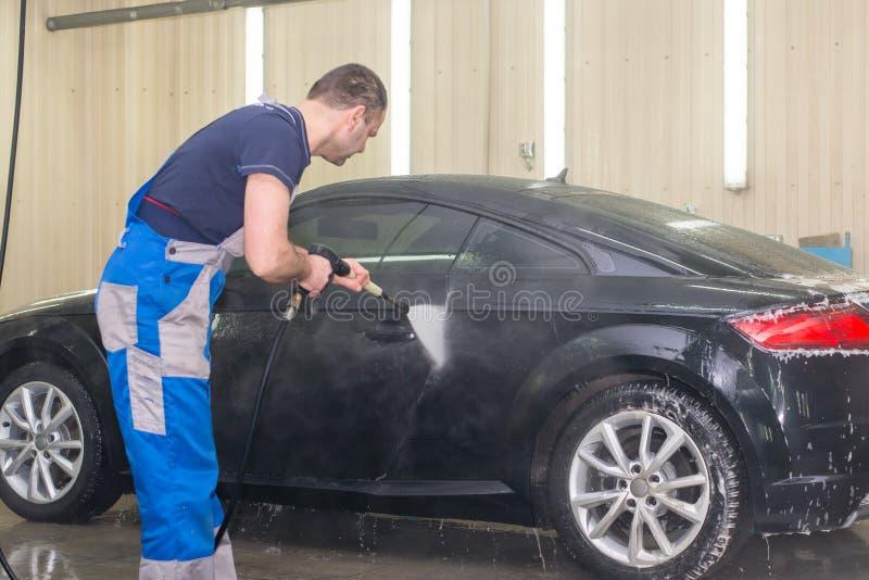 Ένα άτομο πλένει ένα μαύρο αυτοκίνητο στοκ φωτογραφίες