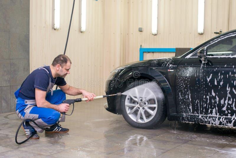 Ένα άτομο πλένει ένα μαύρο αυτοκίνητο στοκ εικόνα με δικαίωμα ελεύθερης χρήσης