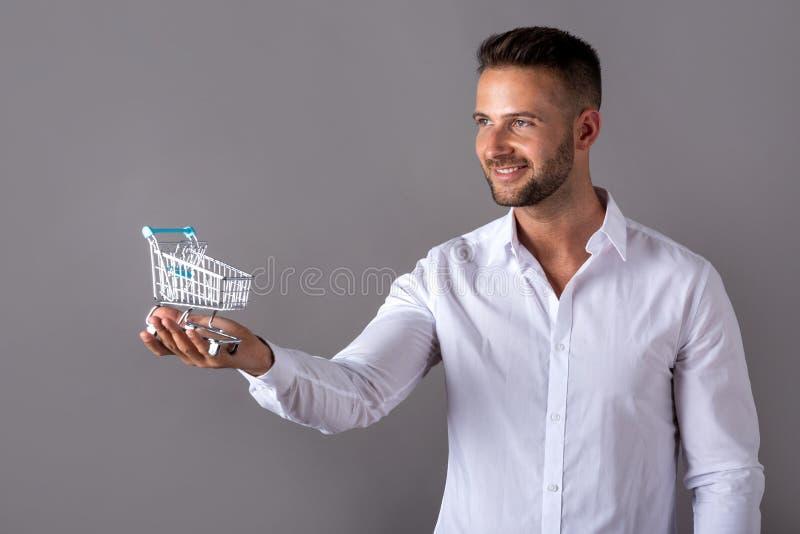 Ένα άτομο σε ένα άσπρο πουκάμισο που κρατά ένα μίνι κάρρο αγορών στοκ φωτογραφία