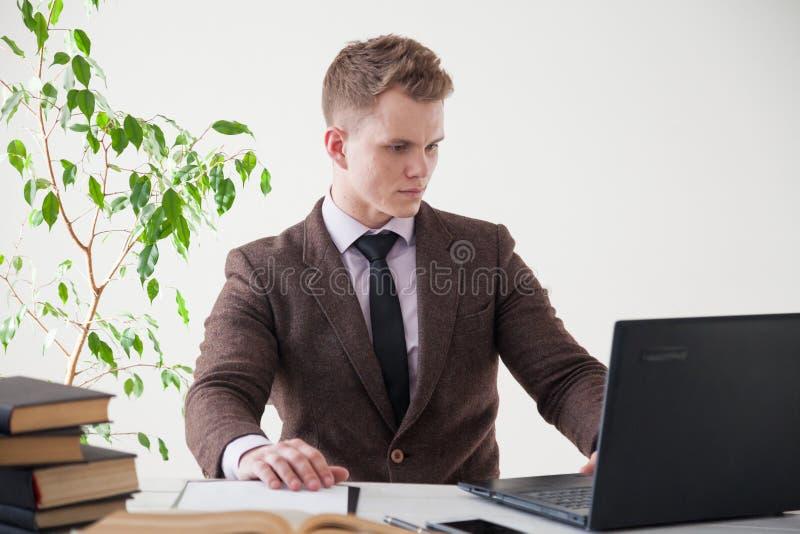 Ένα άτομο σε ένα επιχειρησιακό κοστούμι εργάζεται σε ένα γραφείο με έναν υπολογιστή και τα βιβλία στο γραφείο στοκ φωτογραφίες με δικαίωμα ελεύθερης χρήσης