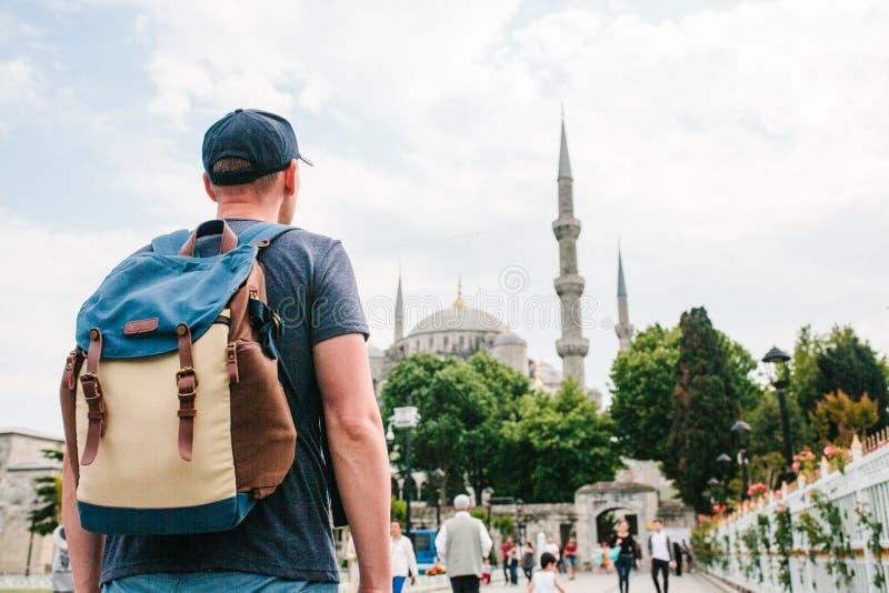 Ένα άτομο σε ένα καπέλο του μπέιζμπολ με ένα σακίδιο πλάτης δίπλα στο μπλε μουσουλμανικό τέμενος είναι μια διάσημη θέα στη Ιστανμ στοκ φωτογραφία