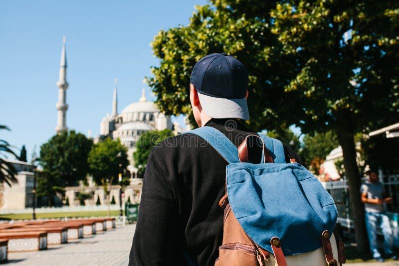 Ένα άτομο σε ένα καπέλο του μπέιζμπολ με ένα σακίδιο πλάτης δίπλα στο μπλε μουσουλμανικό τέμενος είναι μια διάσημη θέα στη Ιστανμ στοκ εικόνα