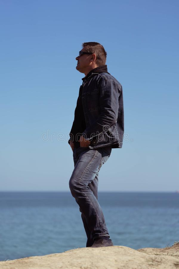 Ένα άτομο σε ένα κοστούμι τζιν στο υπόβαθρο της θάλασσας σε ηλιόλουστο ημερησίως άνοιξη στοκ φωτογραφία