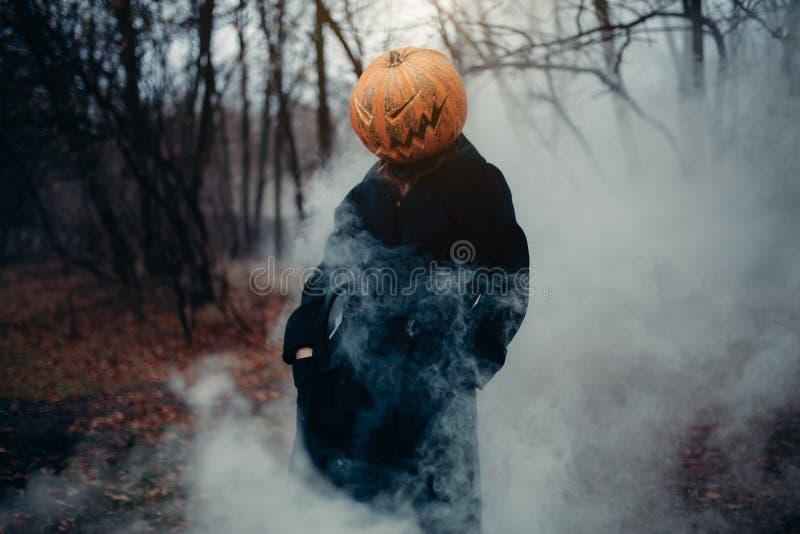 Ένα άτομο σε ένα μακρύ μαύρο παλτό με μια κολοκύθα αντί ενός κεφαλιού σε ένα φοβερές δάσος, μια υγρασία και μια ομίχλη νύχτας στοκ εικόνες με δικαίωμα ελεύθερης χρήσης