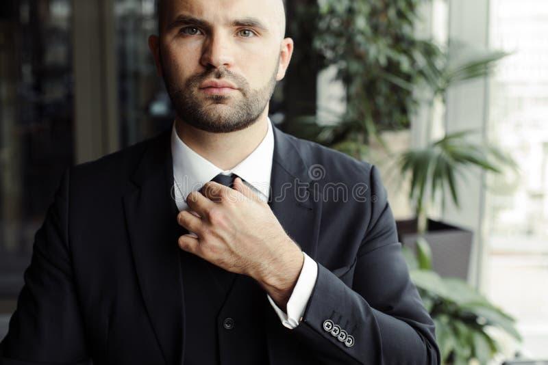Ένα άτομο σε ένα μαύρο κοστούμι ισιώνει το δεσμό του στοκ φωτογραφίες