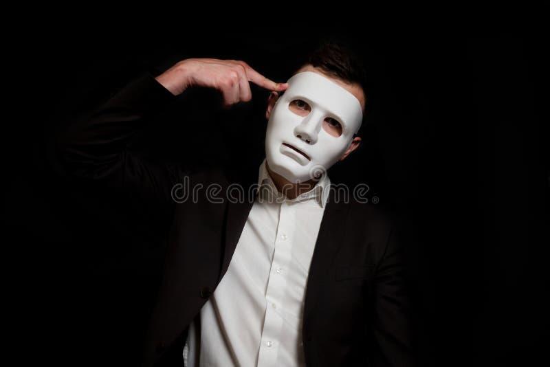 Ένα άτομο σε μια άσπρη μάσκα σε ένα μαύρο υπόβαθρο στρίβει τα δάχτυλά του στο κεφάλι στοκ φωτογραφίες με δικαίωμα ελεύθερης χρήσης