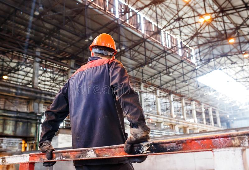 Ένα άτομο σε μια λειτουργώντας μορφή στο υπόβαθρο μεταλλουργικών εγκαταστάσεων κουρασμένος του εργαζομένου εργασίας στοκ φωτογραφίες