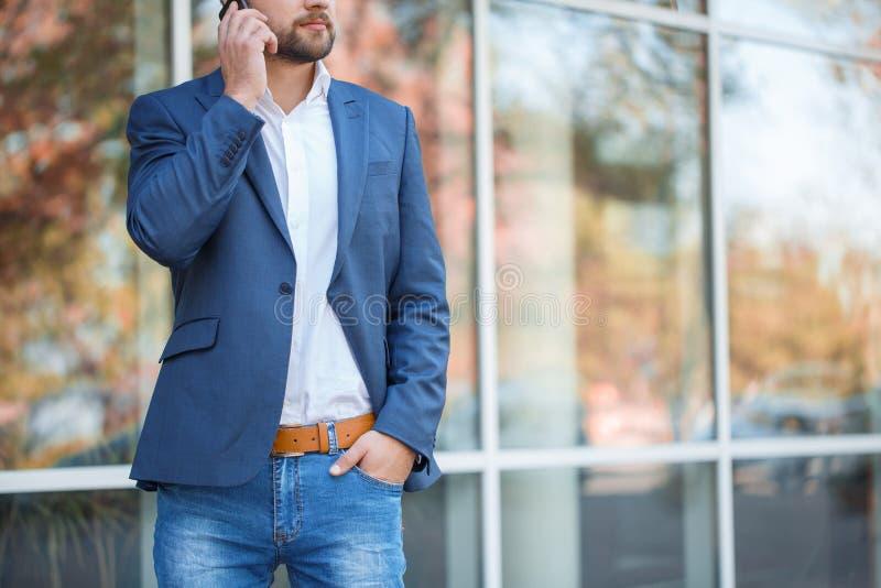 Ένα άτομο σε μια μπλε ζακέτα στην οδό και ομιλία στο τηλέφωνο στοκ εικόνα με δικαίωμα ελεύθερης χρήσης
