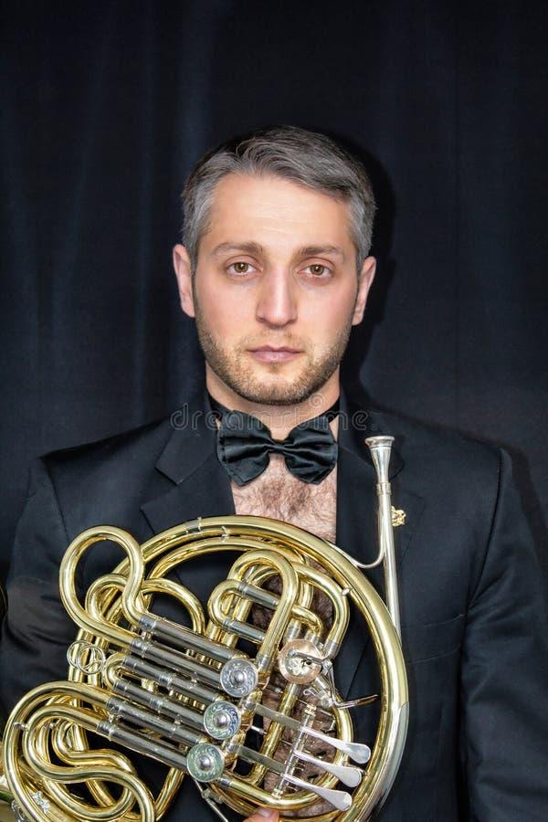 Ένα άτομο σε ένα σακάκι στο γυμνό σώμα του, που κρατά ένα μουσικό όργανο Waldhorn στοκ φωτογραφία