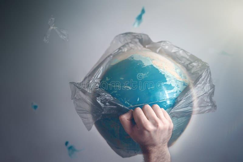 Ένα άτομο σπάζει μια τσάντα απορριμάτων που είναι τυλιγμένη σφαίρα του πλανήτη Γη Η έννοια της οικολογίας και ρύπανση να περιβάλε στοκ εικόνα