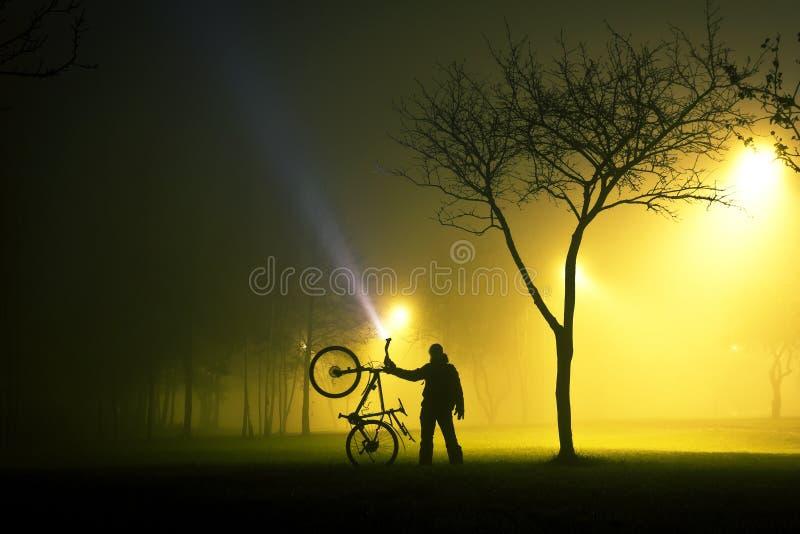 Ένα άτομο στέκεται και κρατά το ποδήλατο στο ομιχλώδες και μυστήριο πάρκο στοκ φωτογραφία με δικαίωμα ελεύθερης χρήσης