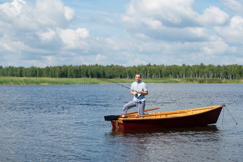 Ένα άτομο στέκεται σε μια ξύλινη βάρκα στη μέση της λίμνης και την αλιεία για την περιστροφή στοκ εικόνες με δικαίωμα ελεύθερης χρήσης
