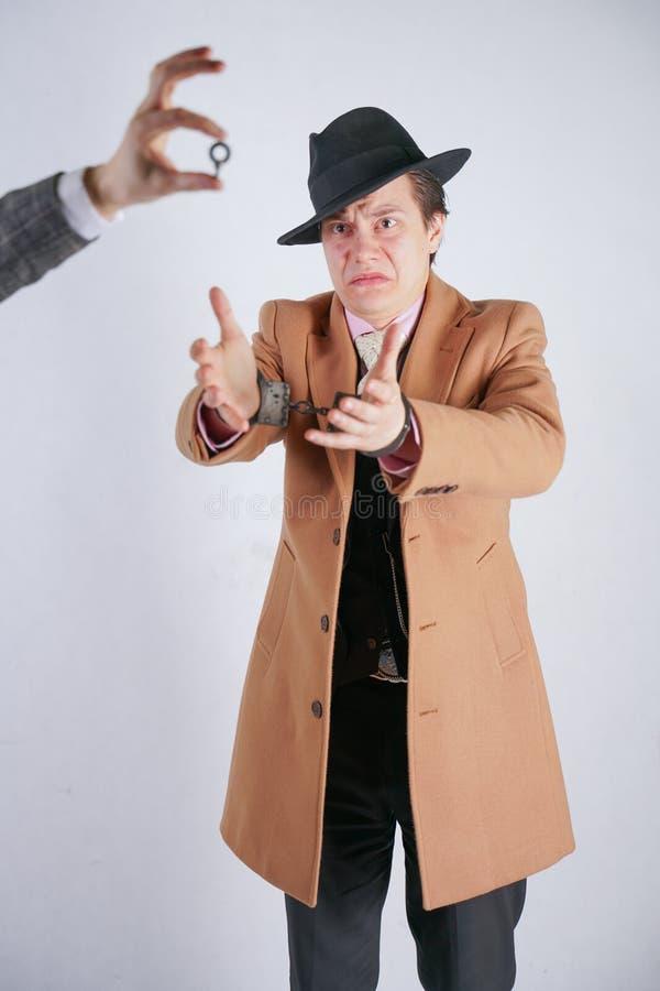 Ένα άτομο συνέλαβε άλλου με την τοποθέτηση στις χειροπέδες ενός αστυνομίας χάλυβα και τη χλεύη με την παρουσίαση του του κλειδιού στοκ εικόνα