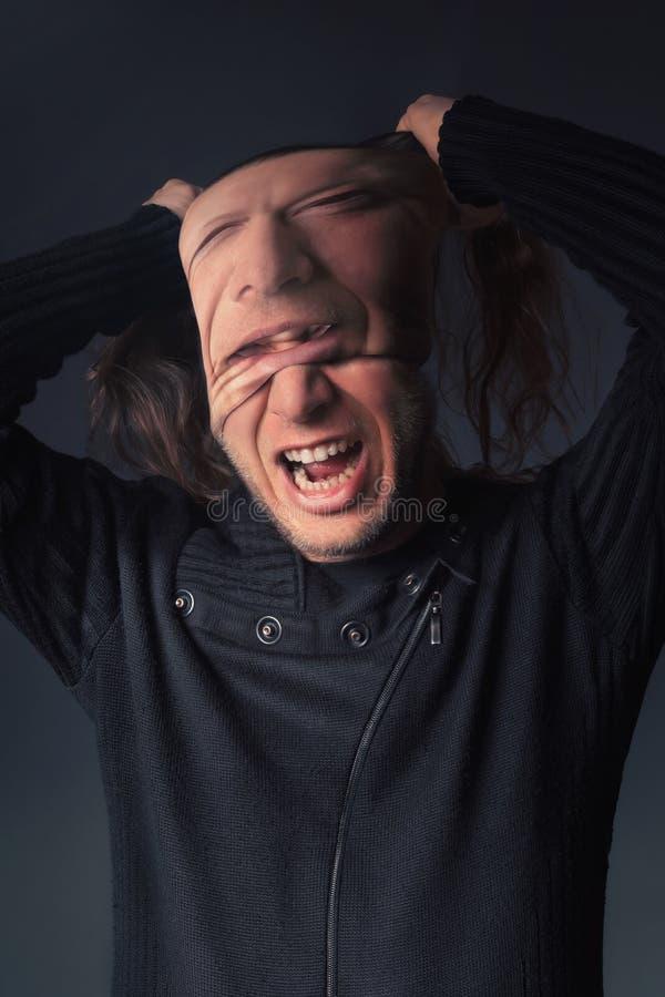 Ένα άτομο σχίζει από τη μάσκα από το πρόσωπό του στοκ φωτογραφία με δικαίωμα ελεύθερης χρήσης
