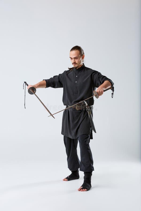 Ένα άτομο ninja, σε ένα μαύρο κιμονό, κρατά δύο παλαιές σκουριασμένες λεπίδες με το πέρασμα της άκρης λεπίδων τους στοκ φωτογραφίες