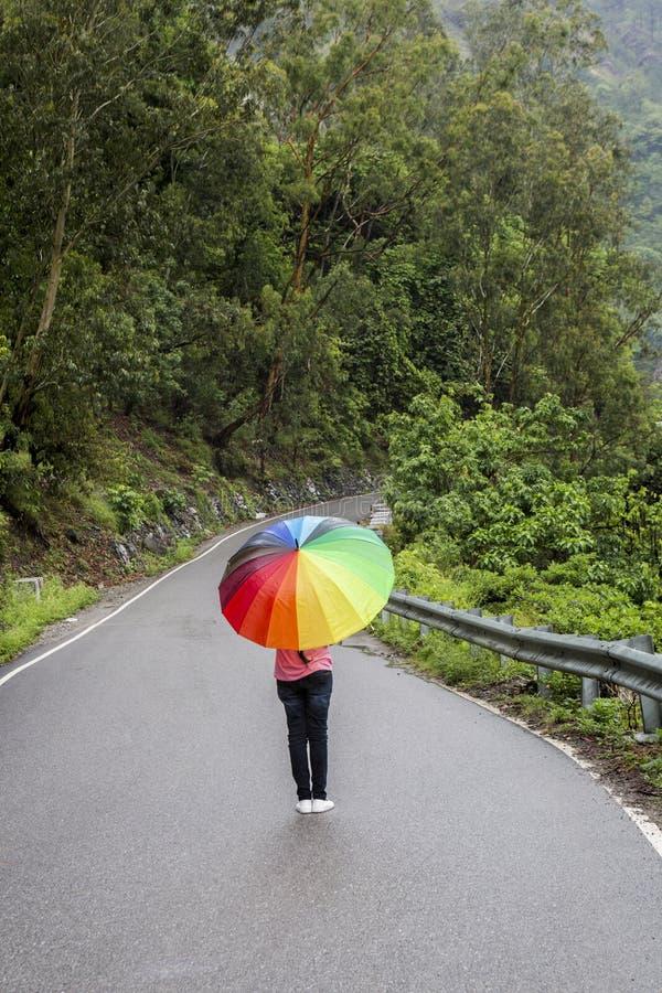 Ένα έφηβη με τη ζωηρόχρωμη ομπρέλα στοκ εικόνες